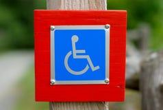 Símbolo azul inhabilitado muestra de la desventaja de la silla de ruedas Imágenes de archivo libres de regalías