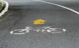 Símbolo blanco de la bicicleta en el camino fotografía de archivo