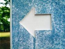 Símbolo branco da seta no cargo de sinal ciano velho fotos de stock royalty free