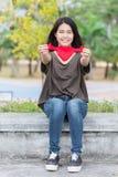 Símbolo cariñoso dulce de la mujer de la mano del corazón rojo hermoso asiático del control Foto de archivo