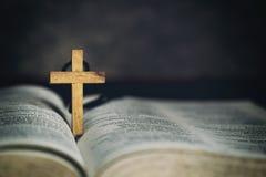 Símbolo cruzado de madera de la muestra y rogación a dios con una biblia en la dedicación de la mañana imágenes de archivo libres de regalías