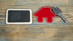 Símbolo da casa com chave de prata no fundo de madeira do vintage imagens de stock