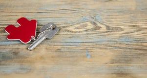 Símbolo da casa com chave de prata no fundo de madeira do vintage foto de stock