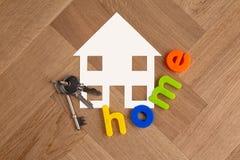 Símbolo da casa com chaves no assoalho de madeira imagens de stock royalty free