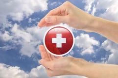 Símbolo da cruz vermelha nas mãos humanas contra o céu Fotografia de Stock Royalty Free