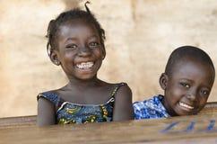 Símbolo da felicidade: Pares de crianças africanas que riem da escola Imagens de Stock