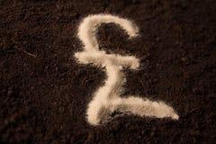Símbolo da libra do logotipo escrito no fundo de terra da areia Fotografia de Stock