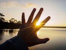 Símbolo da mão contra a luz solar Foto de Stock