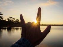 Símbolo da mão contra a luz solar no nascer do sol Foto de Stock