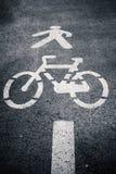Símbolo da pista do pedestre e do ciclo no asfalto Foto de Stock