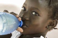 Símbolo da pobreza: Menina preta africana que bebe a água fresca coberta de urzes fotografia de stock