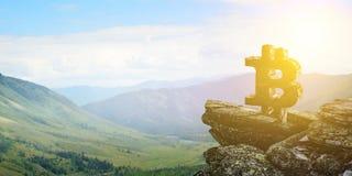 Símbolo de Bitcoin em uma montanha fotografia de stock royalty free