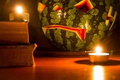 Símbolo de Halloween, sandía con la cara sonriente roja tallada y velas ardientes en fondo oscuro Fotos de archivo
