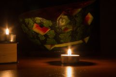 Símbolo de Halloween, sandía con la cara sonriente roja tallada y velas ardientes en fondo oscuro Imagenes de archivo
