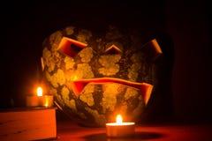Símbolo de Halloween, sandía con la cara sonriente roja tallada y velas ardientes en fondo oscuro Imagen de archivo