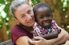 Símbolo de la adopción - la mujer adopta a un pequeño muchacho africano Foto de archivo libre de regalías