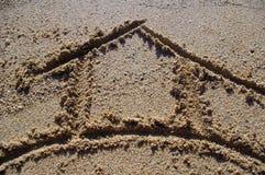 Símbolo de la casa drenado en arena Imágenes de archivo libres de regalías