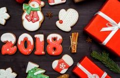 Símbolo de la muestra de la Feliz Año Nuevo 2018 con las galletas rojas y blancas del pan de jengibre en el fondo de madera oscur Foto de archivo libre de regalías
