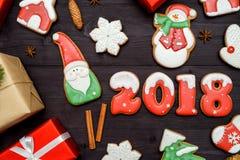 Símbolo de la muestra de la Feliz Año Nuevo 2018 con las galletas rojas y blancas del pan de jengibre en el fondo de madera oscur Imágenes de archivo libres de regalías
