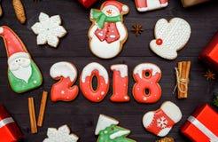 Símbolo de la muestra de la Feliz Año Nuevo 2018 con las galletas rojas y blancas del pan de jengibre en el fondo de madera oscur Fotografía de archivo