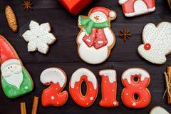 Símbolo de la muestra de la Feliz Año Nuevo 2018 con las galletas rojas y blancas del pan de jengibre en el fondo de madera oscur Fotos de archivo