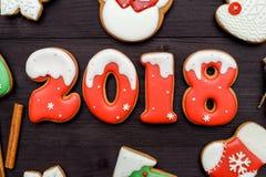 Símbolo de la muestra de la Feliz Año Nuevo 2018 con las galletas rojas y blancas del pan de jengibre en el fondo de madera oscur Imagen de archivo