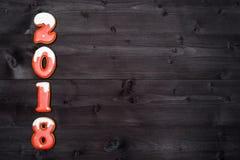 Símbolo de la muestra de la Feliz Año Nuevo 2018 de las galletas rojas y blancas del pan de jengibre en el fondo de madera oscuro Fotografía de archivo