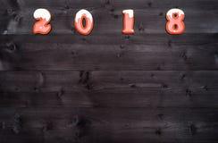 Símbolo de la muestra de la Feliz Año Nuevo 2018 de las galletas rojas y blancas del pan de jengibre en el fondo de madera oscuro Imágenes de archivo libres de regalías