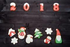 Símbolo de la muestra de la Feliz Año Nuevo 2018 de las galletas rojas y blancas del pan de jengibre en el fondo de madera oscuro Foto de archivo libre de regalías