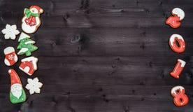 Símbolo de la muestra de la Feliz Año Nuevo 2018 de las galletas rojas y blancas del pan de jengibre en el fondo de madera oscuro Imagenes de archivo