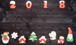 Símbolo de la muestra de la Feliz Año Nuevo 2018 de las galletas rojas y blancas del pan de jengibre en el fondo de madera oscuro Imagen de archivo