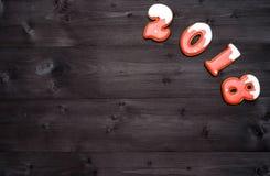 Símbolo de la muestra de la Feliz Año Nuevo 2018 de las galletas rojas y blancas del pan de jengibre en el fondo de madera oscuro Foto de archivo