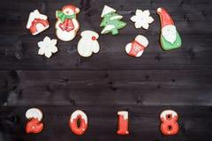 Símbolo de la muestra de la Feliz Año Nuevo 2018 de las galletas rojas y blancas del pan de jengibre en el fondo de madera oscuro Fotos de archivo