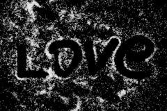 Símbolo de la palabra del amor que dibuja por el finger en el polvo blanco de la sal en fondo negro del tablero imágenes de archivo libres de regalías