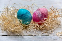 Símbolo de la vida - dos huevos en colores pastel-pintados - rosa y azul en un fondo ligero suave como símbolo de una nueva vida fotos de archivo libres de regalías