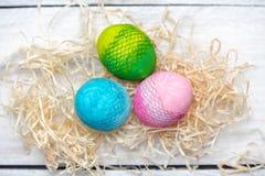 Símbolo de la vida - tres huevos en colores pastel-pintados - rosa, verde y azul en un fondo ligero suave como símbolo de una nue fotos de archivo libres de regalías