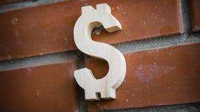 Símbolo de madeira do dólar no fundo da parede de tijolo Foto de Stock Royalty Free