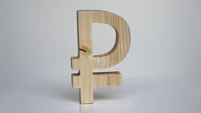 Símbolo de madera de la rublo rusa en un fondo blanco Imágenes de archivo libres de regalías