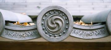Símbolo de Mitsudomoe en la teja de tejado budista sintoísta de la capilla, Japón Imagenes de archivo
