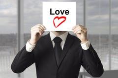 Símbolo de ocultación del corazón del amor de la cara del hombre de negocios Fotos de archivo libres de regalías
