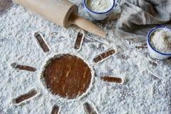 Símbolo de Sun na farinha com os utensílios para cozer imagem de stock