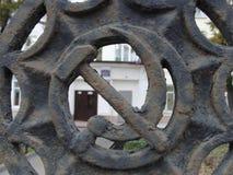 Símbolo de URSS do martelo e da foice na cerca da escola do russo fotografia de stock