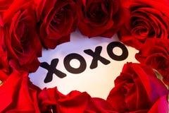 Símbolo de XOXO de los abrazos y de los besos cercados con las rosas rojas foto de archivo libre de regalías