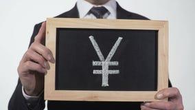 Símbolo de Yuan dibujado en la pizarra en manos del hombre de negocios, moneda china, Asia metrajes