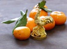 Símbolo del Año Nuevo, del gallo de oro y de las mandarinas Imagen de archivo