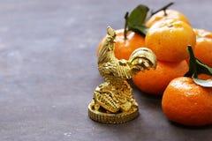 Símbolo del Año Nuevo, del gallo de oro y de las mandarinas Fotos de archivo