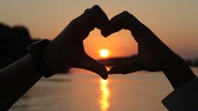 Símbolo del amor, corazón de las manos de amantes en la puesta del sol almacen de video