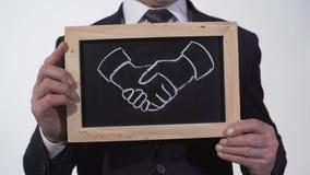 Símbolo del apretón de manos dibujado en la pizarra en manos del hombre de negocios, cooperación eficaz almacen de metraje de vídeo