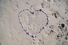 S?mbolo del coraz?n de las formas de las conchas marinas en la playa arenosa fotografía de archivo libre de regalías