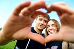 Símbolo del corazón de las manos de un par cariñoso Foto de archivo libre de regalías